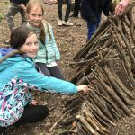 Children building a wooden den with sticks